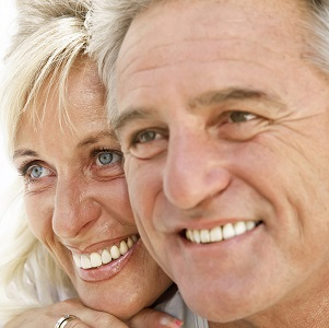 Older couple smiling because of quality New York restorative dentistry treatments