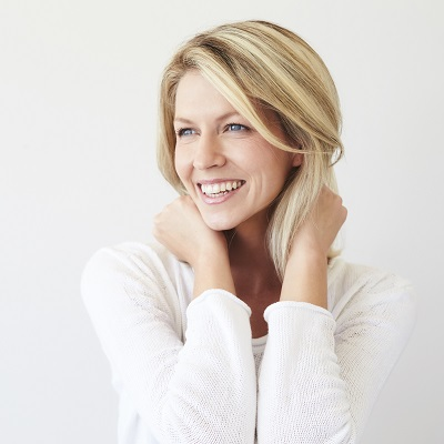 Woman smiling with a full of set of teeth because of dental bridges.
