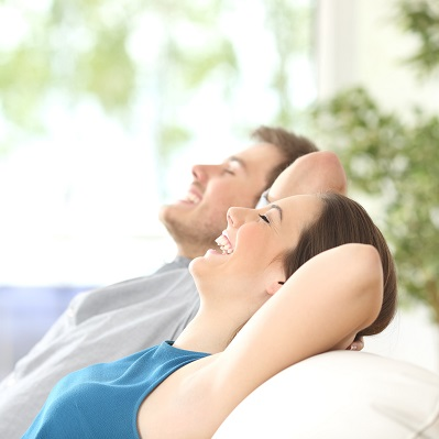 Couple leaning back on sofa and relaxing due to the effects of sedation dentistry.