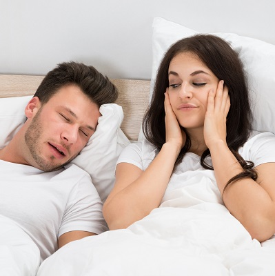 Woman covering ears because of husbands snoring due to sleep apnea.