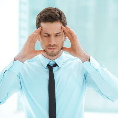 Man holding head because of headache pain caused by TMJ disorder.