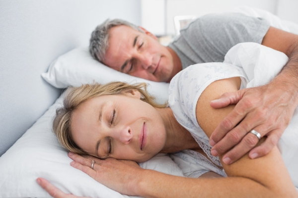 Older man and woman sleeping peacefully in their bed.