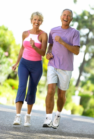 Older man and woman exercising by brisk walking on a road.